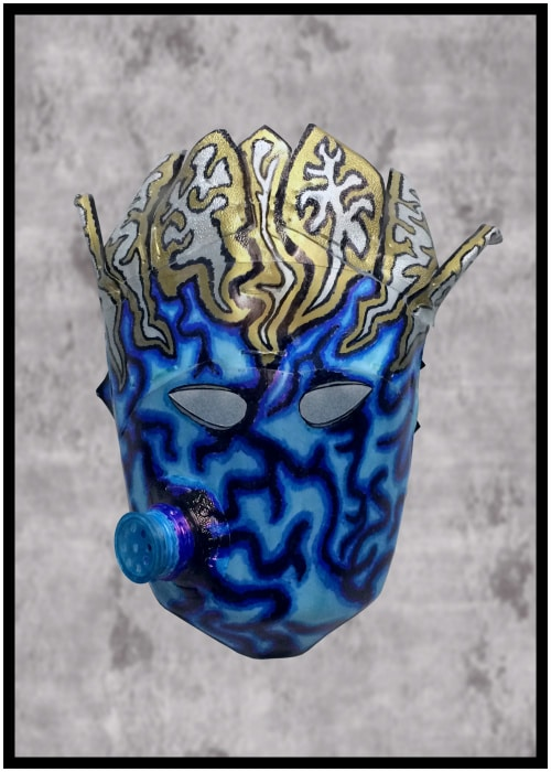Small blue mask made of water bottle plastic. Wiggly black patterns on face with bottle spout coming out right cheek. Golden, silver, and black designs on crown-like forehead.