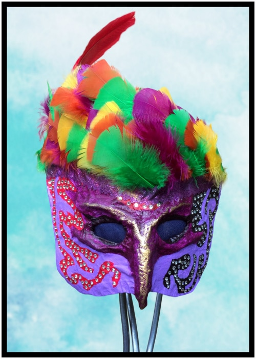 Front of purple mask with feathers and rhinestones.