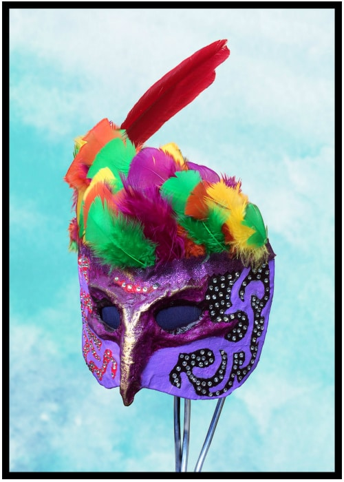Left front of purple cloth-mache mask with colorful feathers. Two large red feathers are on the top. Golden metallic highlights decorate its nose and eyebrows. Black pattern on left cheek decorated with rhinestones. Mask covers top half of face only.