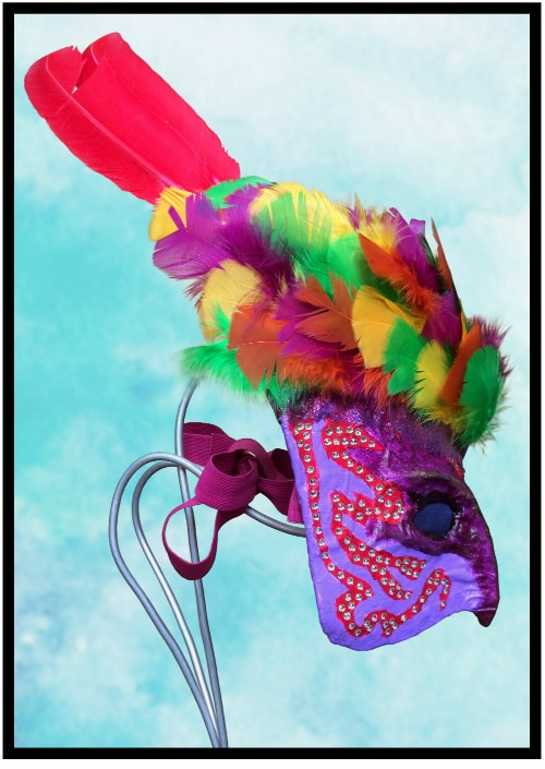 Right side of mask. Red pattern on right cheek decorated with rhinestones. Two large red feathers come out the top of the mask. Pink elastic strapping visible.