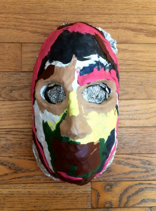 Homemade head form for building mask covered in bright, multi-colored clay.
