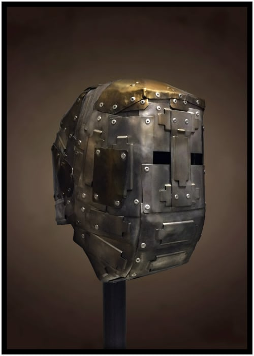 Boxy metal mask made of many small plates riveted together. Steel with brass on side and top of head.