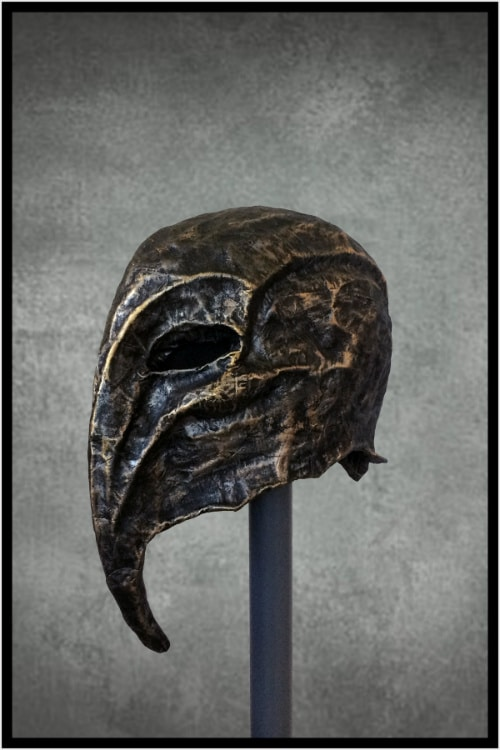 Left front of black cloth-mache mask with long, thin curved beak pointed downward. It has prominent cheekbones, and golden-copper metallic highlights.