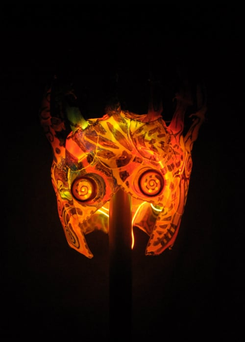 Mask in total darkness. Internally illuminated. It appears almost totally orange with some black patterning on the surface.