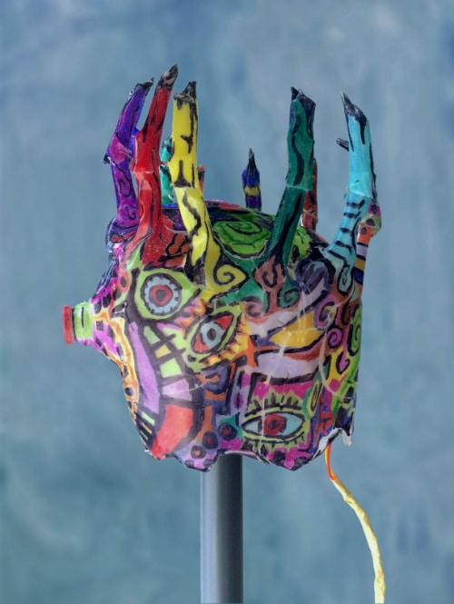 Left side of mask. It has colorful eyes and curling patterns are drawn on it. A cord comes out the back.