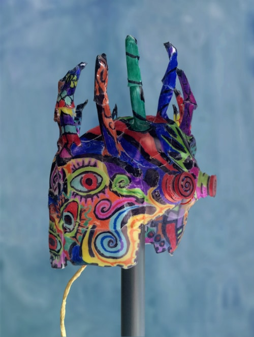 Right side of mask. It has colorful eyes and curling patterns are drawn on it. A cord comes out the back.