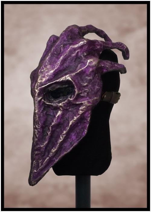 Left front of purple mask. Fingers are visible coming out the knuckles on its head. It appears to cover the wearer's head like a closing hand.