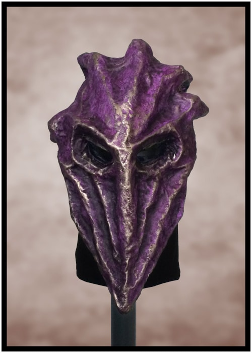Purple mask shaped like reverse teardrop with rectangular eyes and golden highlights.