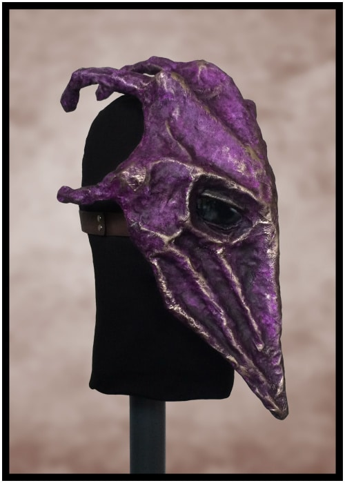 Right front of purple mask. Fingers are visible coming out the knuckles on its head. It appears to cover the wearer's head like a closing hand.
