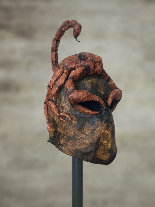 Mottled-brown helmet with red scorpion on top of it. Scorpion's claws form the eye holes for the wearer to see through.