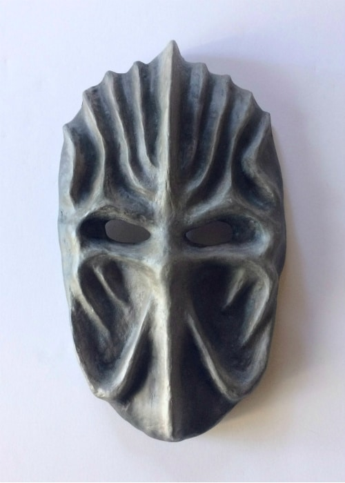 Oval grey papier-mache mask with curving vertical ridges on its forehead and cheeks.
