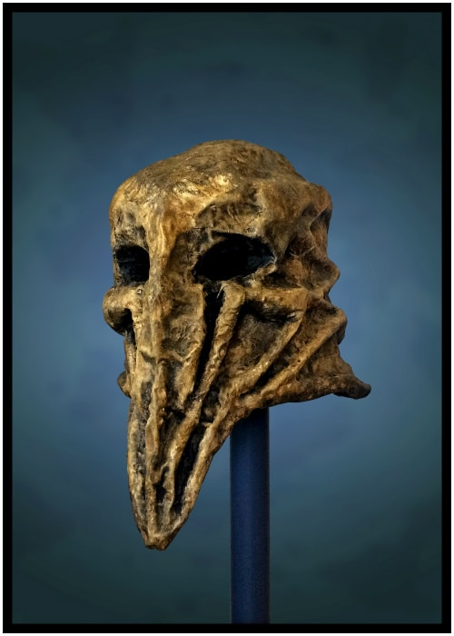 Left front of mask. Ridges run down its face and around its head forming dark, recessed areas.