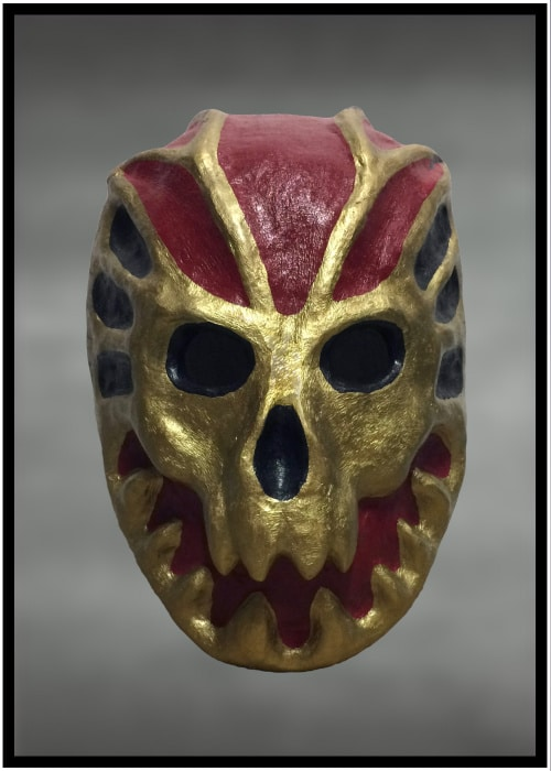 Stylized papier-mache smiling skull mask painted gold, red, and black.