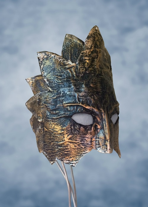 Gunmetal blue cloth-mache mask with golden and copper highlights. Covers top half of face only. Edges cut to form triangular leaf-like patterns. A rhinestone is on the end of each leaf.