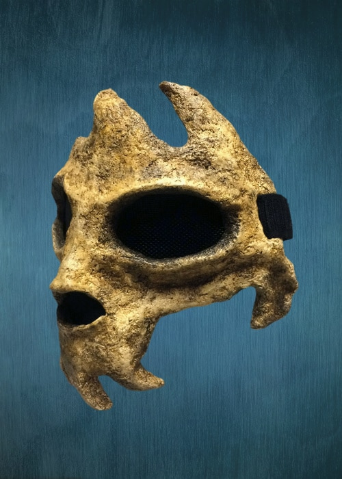 "Left front of mask. There is a small spur of ""bone"" behind the cheek where the jaw would begin."