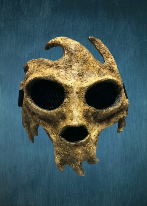Stylized papier-mache skull mask. It has large eyes, a black nose hole, no lower jaw, and three curved front teeth. There are three wave-shaped structures on its forehead that curve in the opposite direction of the teeth.