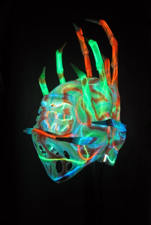 Left front of mask in total darkness, internally illuminated by blue, green, and orange lights.