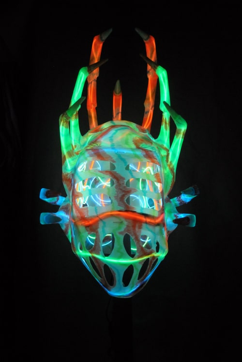 Mask in total darkness, internally illuminated by blue, green, and orange lights. Claws brightly lit.