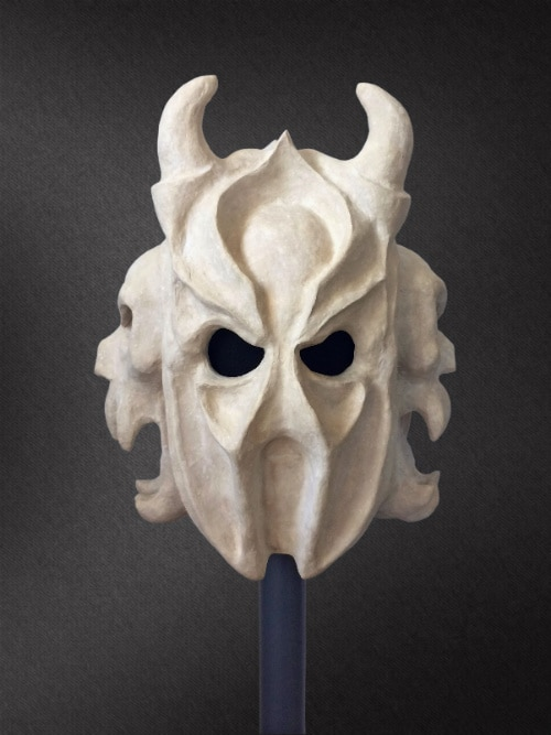Large bone-colored mask with two small horns pointing upward, and a skull face on each side of its head.