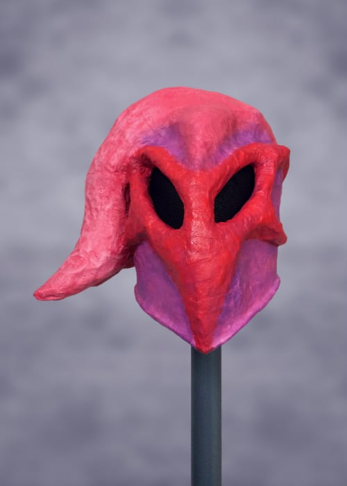 Front of mask. It has a red, heart-shaped face with two large, black eyes that are dramatically tilted downward. Large pink tentacle comes off the top of its head and flows to the left of the picture. There are no tentacles to the right.