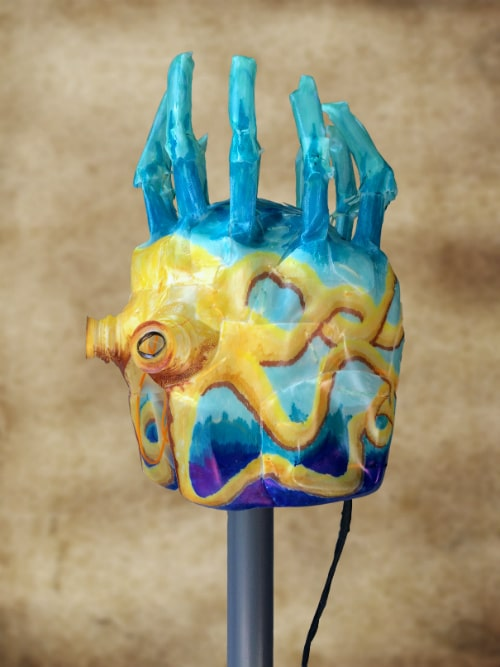 Left side of mask. Yellow tentacles are drawn around the side on blue background. Black cord hangs down from back.