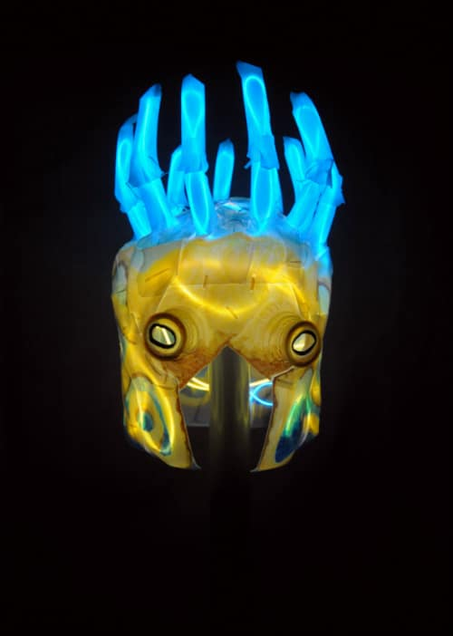 Mask in total darkness. Yellow wires illuminate the octopus face while blue wires illuminate the claws coming out the top of its head.
