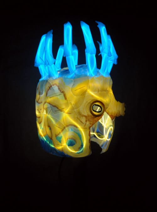 Right front of mask in total darkness. Yellow wires illuminate the octopus face and sides of mask, while blue wires illuminate the claws coming out the top of its head.
