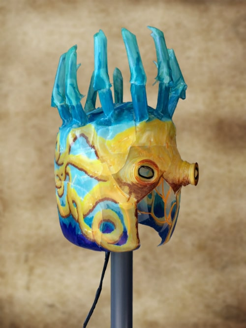 Right front of octopus mask. Yellow tentacles are drawn around the side on blue background. Black cord hangs down from back.