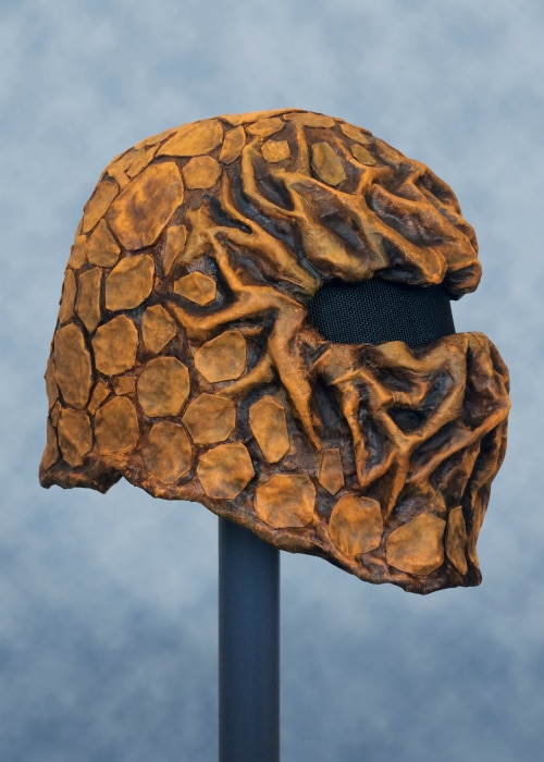 Right front of orange and brown scale mask with roots on face.