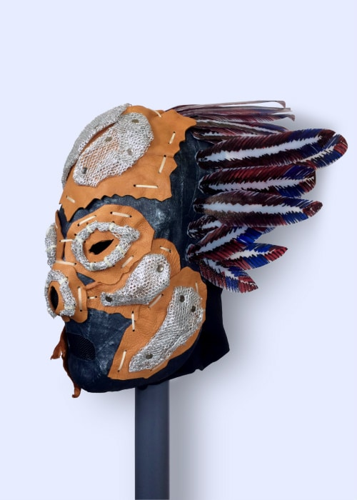 Bluish mask with patches of leather and pieces of metal mesh attached to its face, and plastic feathers coming out the back of its head.