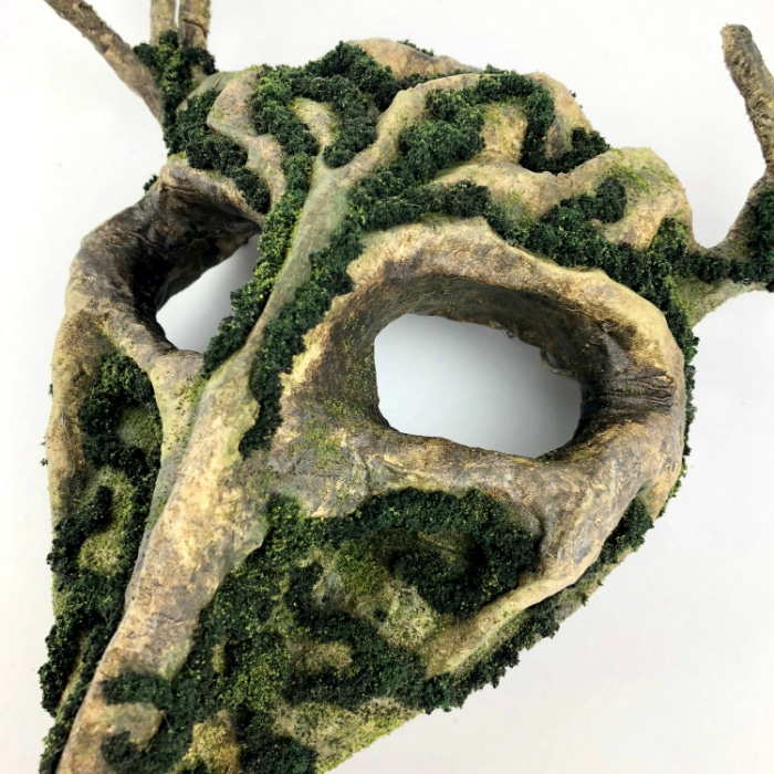 Closeup of mask from left angle. Various mossy textures are visible, along with many shades of brown and green.