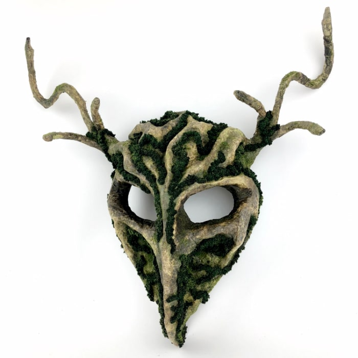 Brown and green mask that's shaped like a stylized bird skull. Curved antlers come out the side of its head.