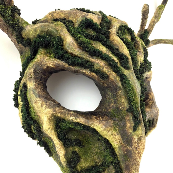Closeup of right front of mask. Various mossy textures are visible, along with many shades of brown and green.