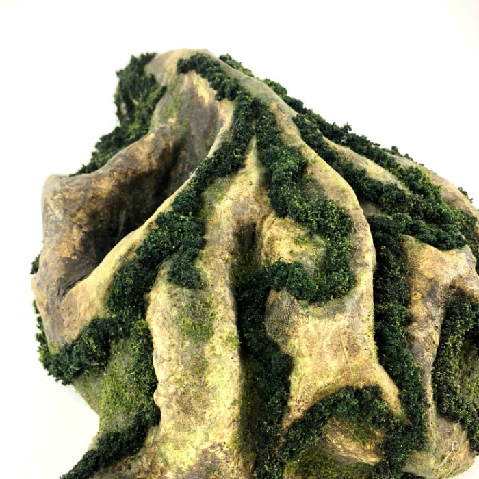 Top view. Mask has a deeply ridged forehead with moss in the valleys, giving it a mountainous appearance.