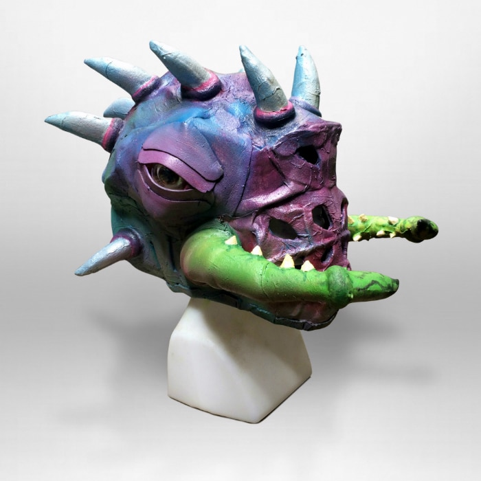 Right angle view of foam mask. It is purple and blue, with silver spikes coming out the top and back of its head. Green pincers wrap around the side of the face, and there are holes in the mouth area. It has a cow-like eye on the side of its head.
