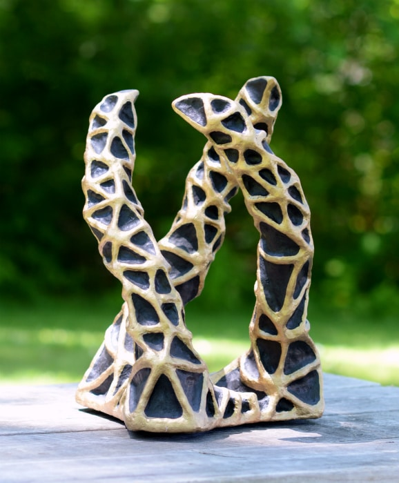 "Sculpture composed of three ""arms"" coming up from a triangular base. They twist around each other in a helix pattern. The sculpture is painted black and covered in gold ridges forming triangular patterns."