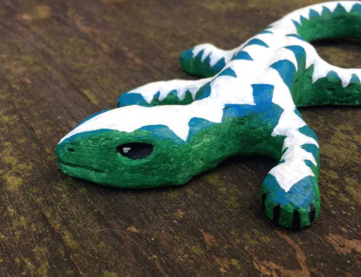 Green-blue lizard with pattern of white triangles on its back, head, legs, and tail.