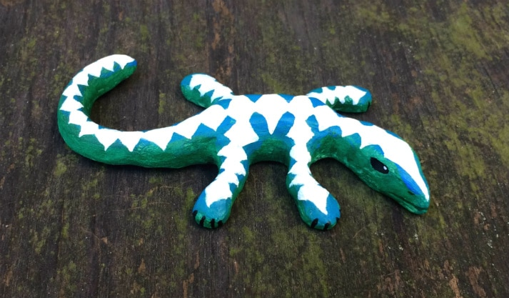 Side view of lizard. It is green with blue on its back, and within the blue it has white diamond-shaped patterns on its head, legs, back, and tail.
