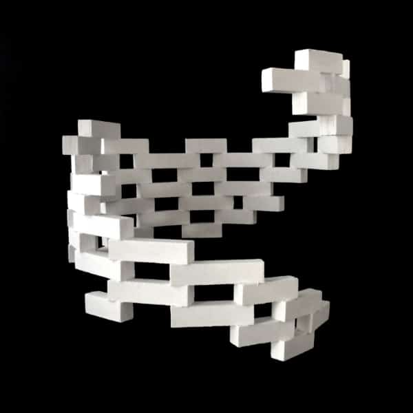 White sculpture made of interlocking wooden blocks on black background. It is semi-circular in shape. From this angle it looks roughly like the letter K.