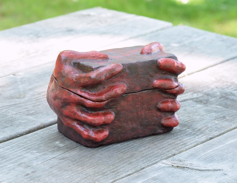 Red box with hands sculpted into the sides that appear to be gripping it. The box is outside on a wooden table.