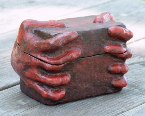 Red box with hands sculpted into the sides that appear to be gripping it.