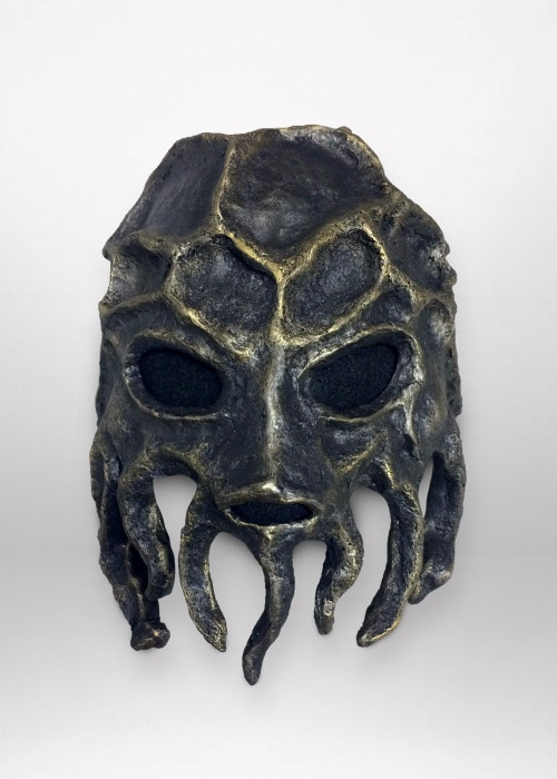 Front of black paper-napkin mask with gold highlights. Its forehead is covered in asymmetrical ridges making oval shapes. The lower half of the mask is made up of twisted tooth-like structures.