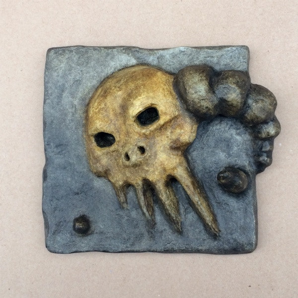 Grey stone-color tile with yellow-brown skull face with horns in it. The face is sunken at an angle, so one of the horns comes out prominently, while the other is submerged.