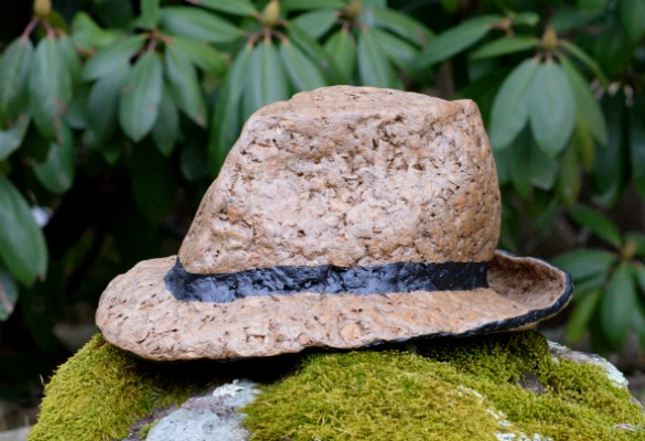 Cardboard fedora. It's brown, and its chunky texture is visible. There's a black band painted around it and black painted on the rim.