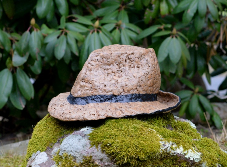Cardboard fedora turned slightly to the left. It's brown, and its chunky texture is visible. There's a black band painted around it and black painted on the rim. It is sitting on a mossy rock with rhododendron leaves in the background.