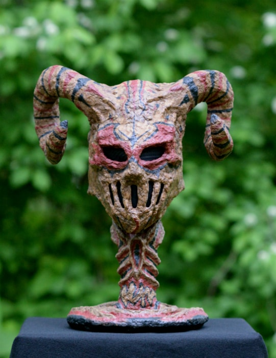 Front view. Titan mask on cardboard sculpture stand. The picture is taken outside with a green leafy background on top of a black box.