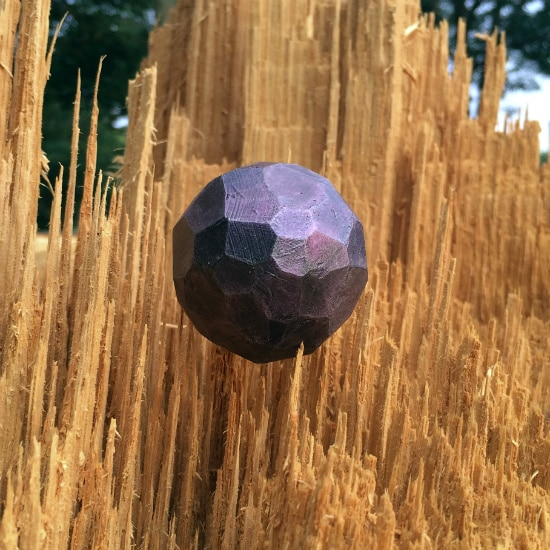 Close up of purple sphere placed in vertically torn wood.