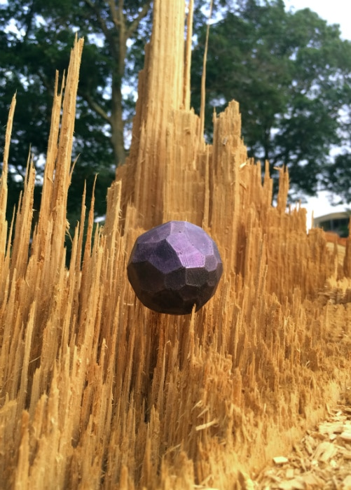 Purple sphere placed in vertically torn wood. It almost looks like it's floating.
