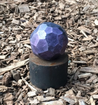 Reflective purple sphere made up of many flat, faceted sides.