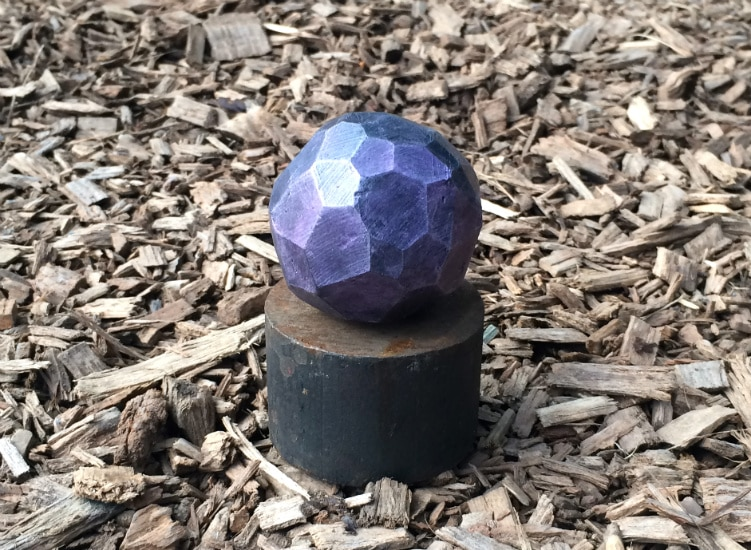 Reflective purple sphere made up of many flat, faceted sides. It is atop a metal cylinder with a background of wood chips.